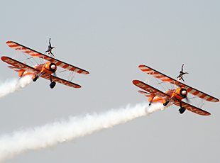 Wingwalkers demonstrating their acrobatic skills in midair