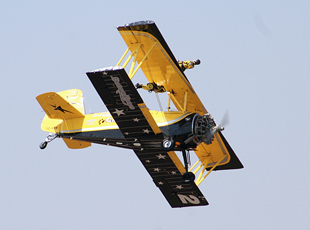 Catwalk Aerobatic Team members perform aerial stunts atop Boeing Stearman biplane